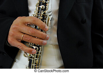 Oboe player - an oboe player holds his oboe on his hand