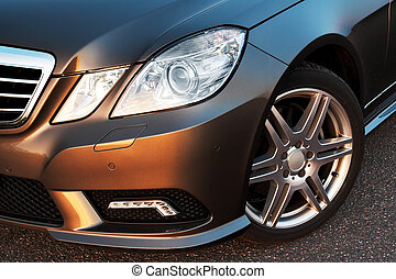 Front wheel, bumper and light detail of a modern sporty...