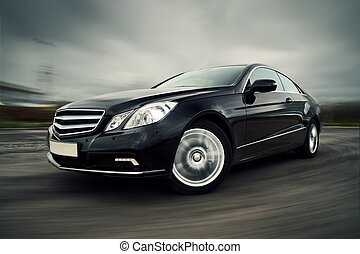 Car driving fast - Front view of black luxury coupe driving...