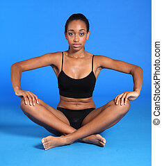 Athletic african fitness woman sits cross legged - Beautiful...