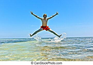boy jumping at a sandbank