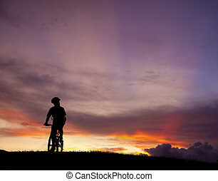 The silhouette of mountain bicycle rider on the hill with beautiful sunrise background