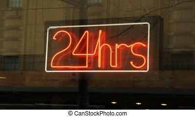 24 hours sign. - Neon 24 hours sign in window. Reflections...