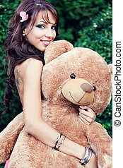 Happy cute woman and her teddy bear - Happy cute young woman...