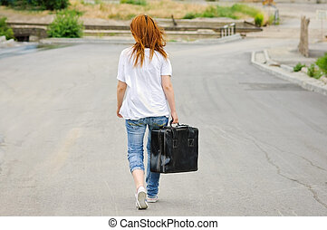 Young girl with suitcase walking down the street. Rear view...
