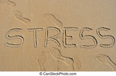 Stress  - The word stress written in the sand on the beach.