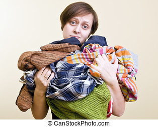 a lot of laundry - woman holds a lot of loundry in her...