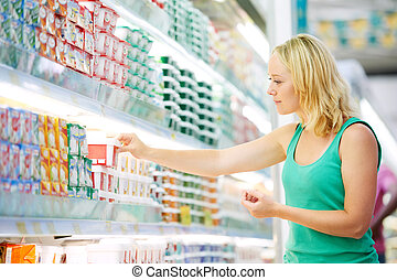 woman making dairy shopping - woman choosing produces in...