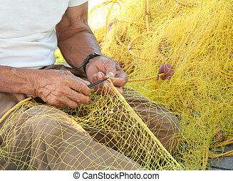 Fisherman Mending His Fishing Net in Greece - A fisherman...