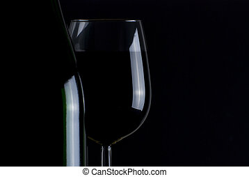 Bottle and glass of red wine isolated on black background