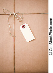 brown paper parcel with a blank luggage tag