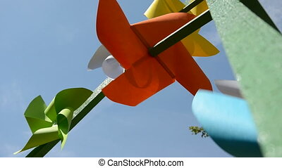 colorful paper windmills on sky background and wind