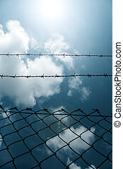 Barbed wire fence against a blue sky with clouds