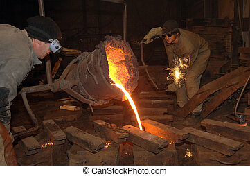 Molten steel pouring - pouring molten metal from a ladle in...