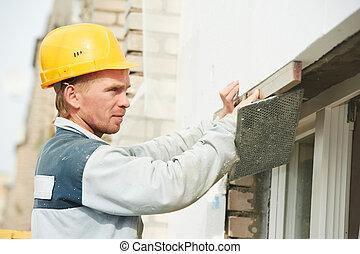 builder facade plasterer worker with level
