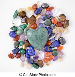 Green quartz heart among various semiprecious gems
