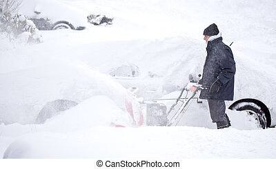 Man blowing snow to clear out sidewalk and driveway