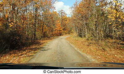 Driving down Autumn road - Driving on an empty rural road in...