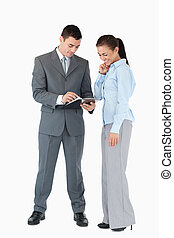 Business partner analyzing documents against a white...