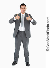 Smiling businessman giving thumbs up against a white...