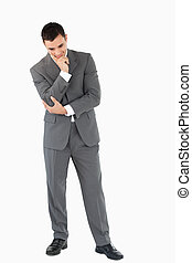 Businessman looking on the floor while thinking against a...