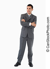 Young businessman with arms folded looking confident against a white background