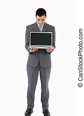 Businessman standing with his laptop against a white background
