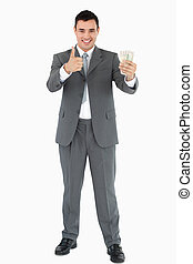 Businessman with banknotes giving thumb up against white...