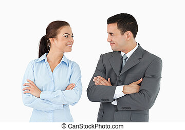 Business partners with arms folded looking at each other...