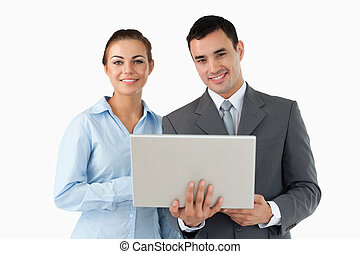 Smiling business partners with laptop against a white...