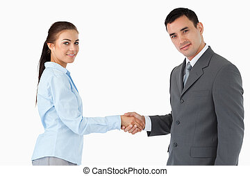 Young business partners shaking hands against a white...