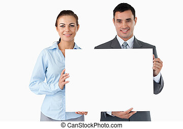 Business partners presenting sign against a white background