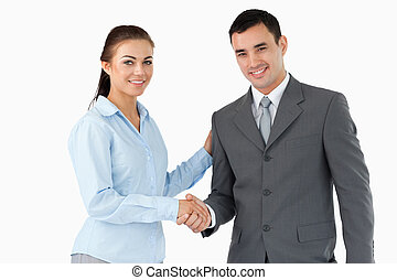 Smiling business partners shaking hands against a white...