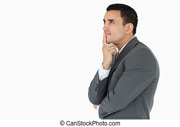 Side view of businessman in thoughts against a white...
