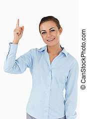 Smiling businesswoman pointing upwards against a white...