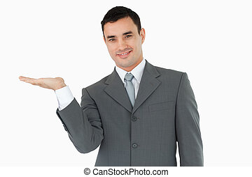 Businessman displaying something in his palm against a white...