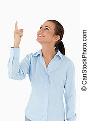 Smiling businesswoman looking and pointing upwards against a...