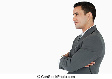 Side view of confident businessman with arms folded against...