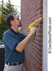 Contractor filling exterior wall cracks - Contractor...