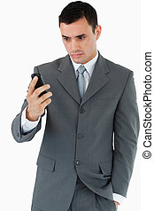 Serious looking businessman looking at his cellphone