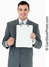 Smiling businessman pointing with pen at clipboard against a...