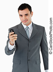 Confident businessman with his cellphone against a white...