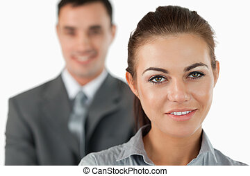 Close up of smiling businesswoman with colleague behind her