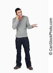 Young male gesturing while on the phone
