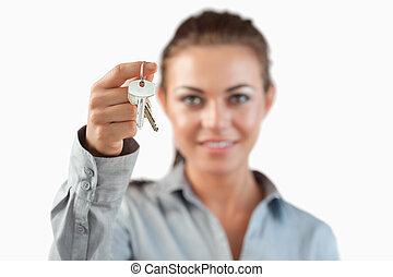 Close up of keys being held by female estate agent against a...