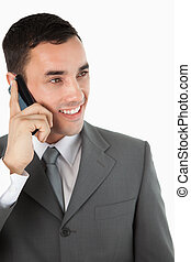 Close up of smiling businessman looking to the side while on the phone against a white background