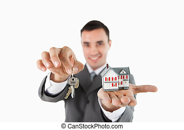 Close up of keys and miniature house being held by male estate agent against a white background