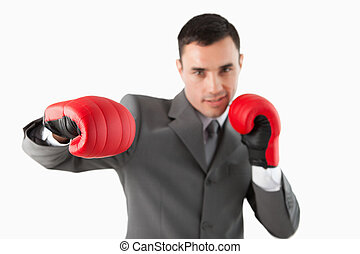 Close up of businessman with boxing gloves striking a hook