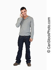 Young male standing while on the phone