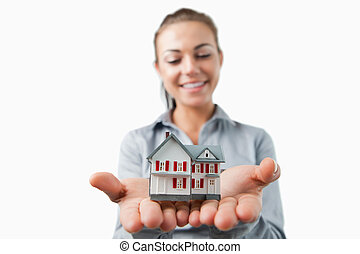 Miniature house being held by young female estate agent...
